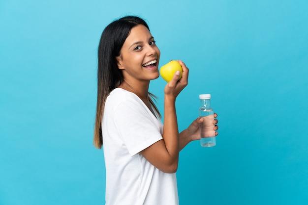 Menina caucasiana isolada em azul com uma maçã e uma garrafa de água