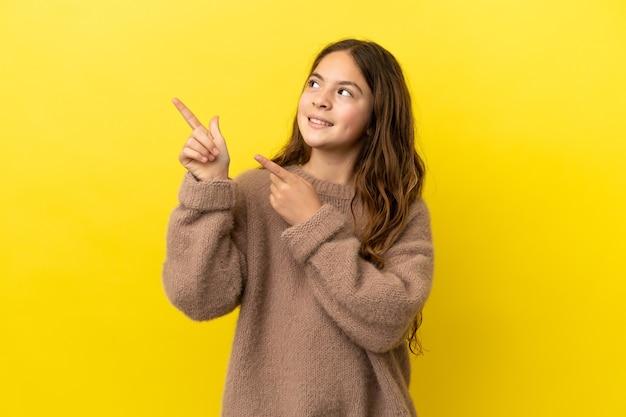 Menina caucasiana isolada em fundo amarelo apontando com o dedo indicador uma ótima ideia