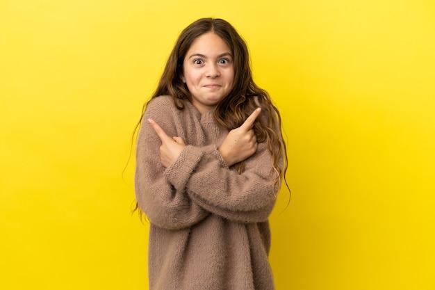 Menina caucasiana isolada em fundo amarelo apontando para as laterais tendo dúvidas