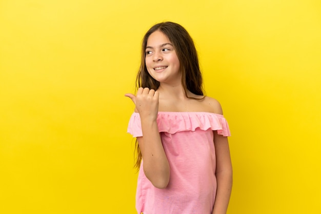 Menina caucasiana isolada em fundo amarelo apontando para o lado para apresentar um produto