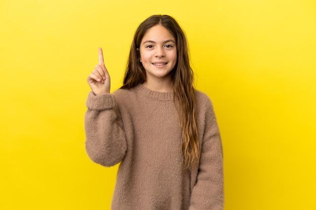 Menina caucasiana isolada em fundo amarelo apontando para uma ótima ideia