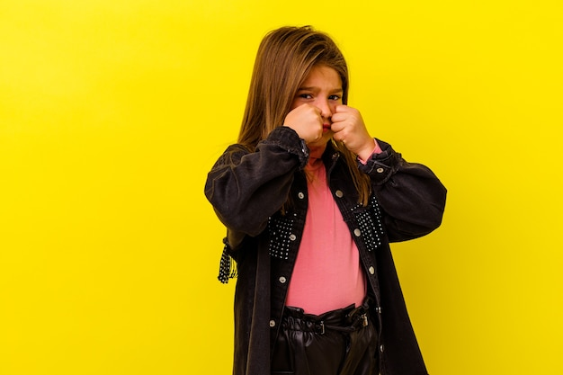 Menina caucasiana isolada em fundo amarelo, chorando e chorando desconsoladamente.