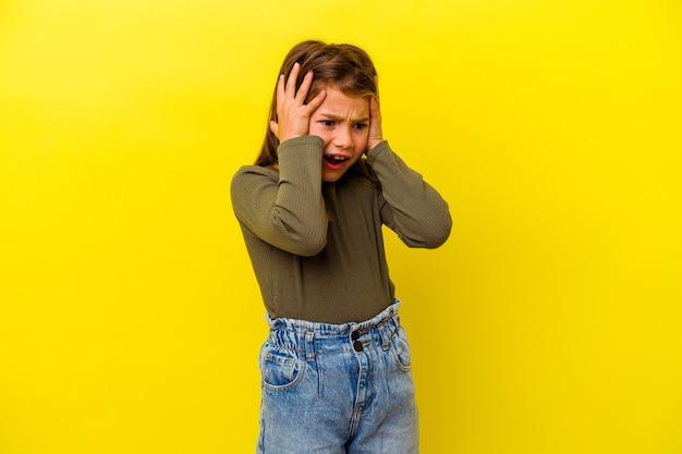 Menina caucasiana isolada em fundo amarelo, cobrindo as orelhas com as mãos, tentando não ouvir o som muito alto.