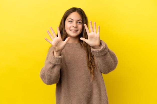 Menina caucasiana isolada em fundo amarelo contando dez com os dedos