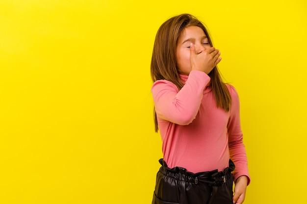 Menina caucasiana isolada em fundo amarelo, rindo de emoção feliz, despreocupada e natural.