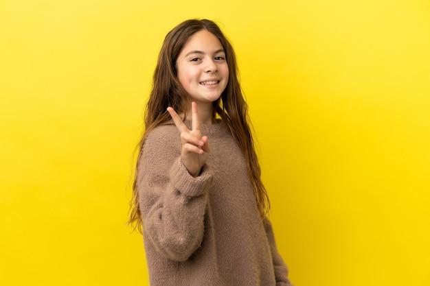 Menina caucasiana isolada em fundo amarelo sorrindo e mostrando sinal de vitória