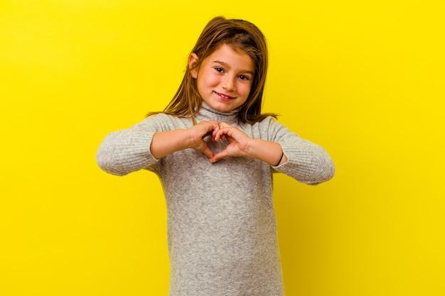 Menina caucasiana isolada em fundo amarelo, sorrindo e mostrando uma forma de coração com as mãos.