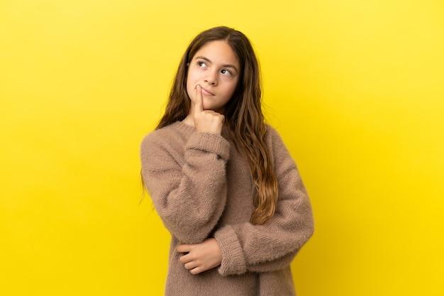 Menina caucasiana isolada em fundo amarelo tendo dúvidas enquanto olha para cima