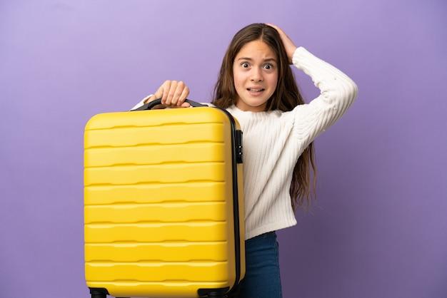Menina caucasiana isolada em fundo roxo de férias com mala de viagem e surpresa