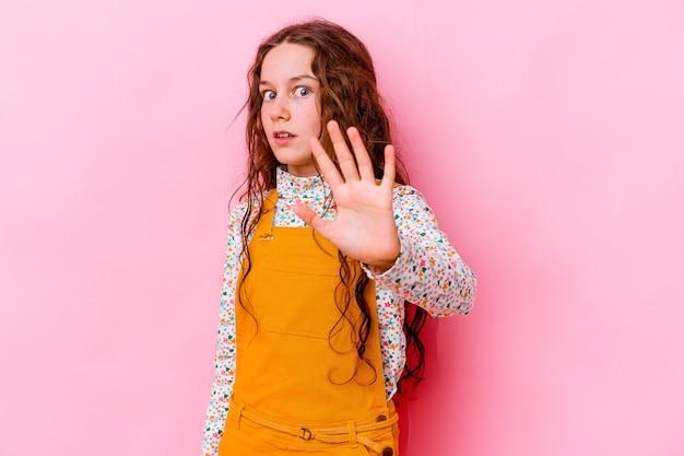 Menina caucasiana isolada em rosa, chocada devido a um perigo iminente