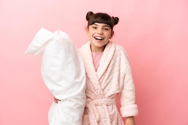 Menina caucasiana isolada em rosa de pijama e com expressão facial surpresa e chocada