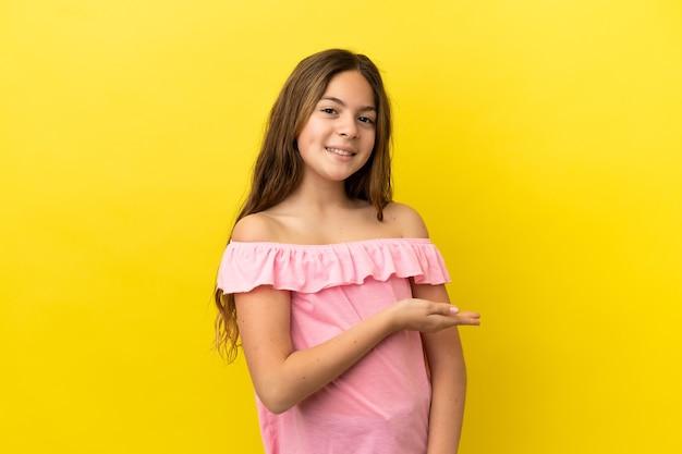 Menina caucasiana isolada em um fundo amarelo, apresentando uma ideia enquanto olha sorrindo para