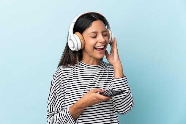 Menina caucasiana isolada em um fundo azul, ouvindo música com um celular e cantando