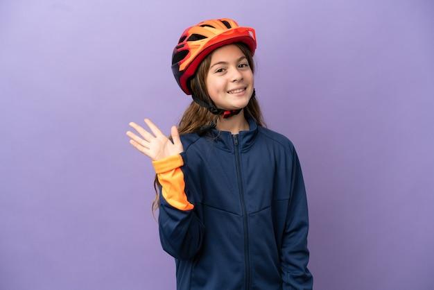 Menina caucasiana isolada em um fundo roxo saudando com uma mão com uma expressão feliz