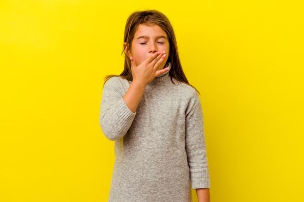 Menina caucasiana isolada na parede amarela bocejando mostrando um gesto cansado, cobrindo a boca com a mão.