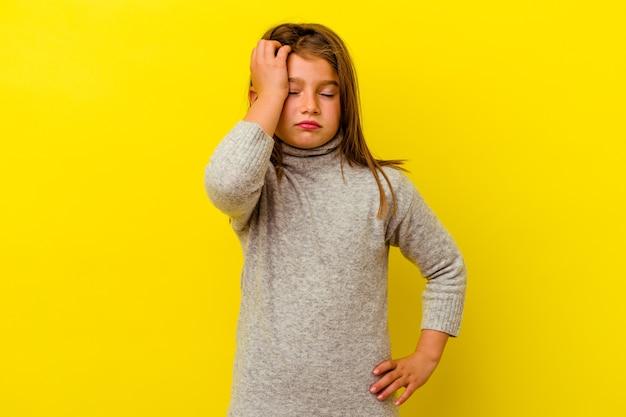 Menina caucasiana isolada na parede amarela, cansada e com muito sono, mantendo a mão na cabeça.