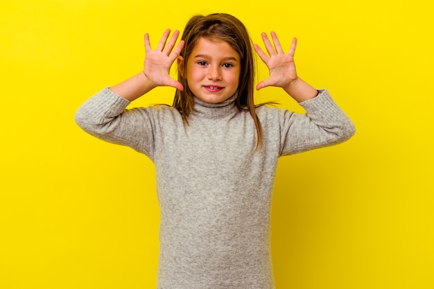 Menina caucasiana isolada na parede amarela, mostrando o número dez com as mãos.