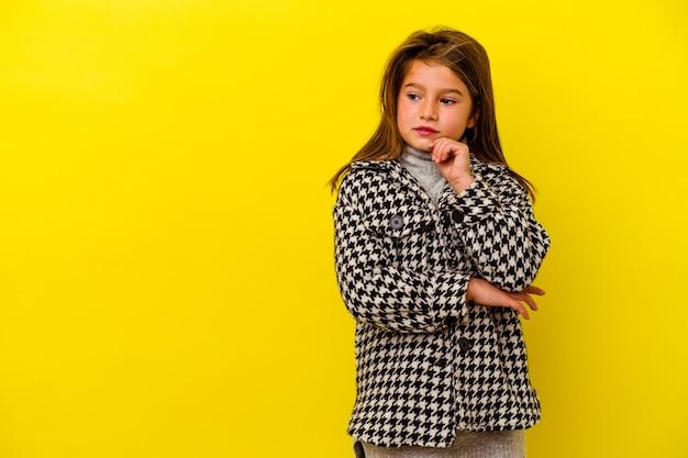 Menina caucasiana isolada na parede amarela, olhando de soslaio com expressão duvidosa e cética.