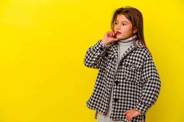 Menina caucasiana isolada na parede amarela relaxada pensando em algo olhando para um espaço de cópia.