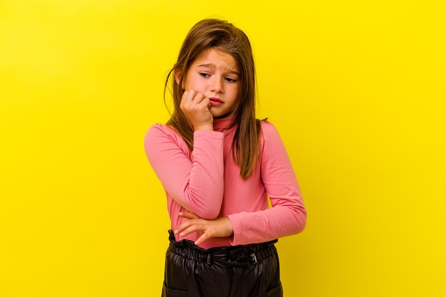 Menina caucasiana isolada na parede amarela, roendo as unhas, nervosa e muito ansiosa.