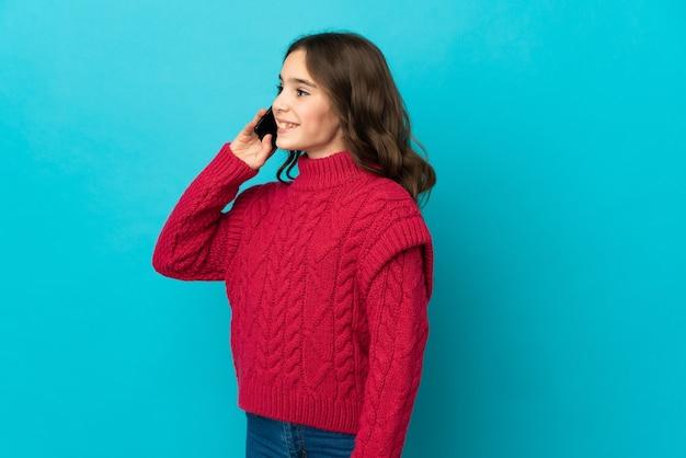 Menina caucasiana isolada na parede azul, conversando com alguém com o celular