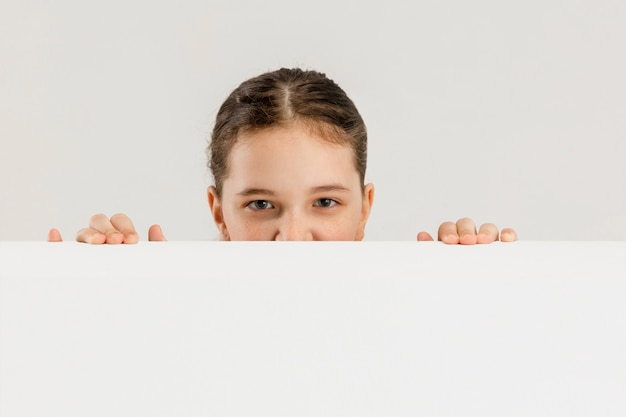 Menina caucasiana isolada na parede branca copyspace educação infantil conceito de emoções