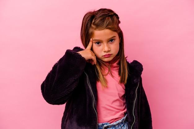 Menina caucasiana isolada na parede rosa, apontando o templo com o dedo, pensando, focada em uma tarefa.