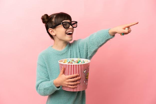 Menina caucasiana isolada na parede rosa com óculos 3d e segurando um grande balde de pipocas enquanto aponta para longe