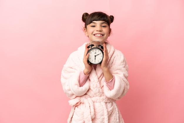 Menina caucasiana isolada na parede rosa de pijama e segurando o relógio com uma expressão feliz
