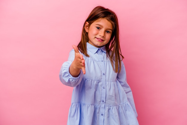 Menina caucasiana isolada na parede rosa, esticando a mão para a câmera em um gesto de saudação.