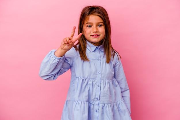 Menina caucasiana isolada na parede rosa, mostrando o número dois com os dedos.