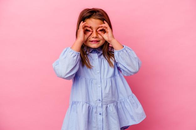 Menina caucasiana isolada na parede rosa mostrando sinal de aprovação sobre os olhos