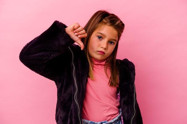 Menina caucasiana isolada na parede rosa, mostrando um gesto de antipatia, polegares para baixo. conceito de desacordo.