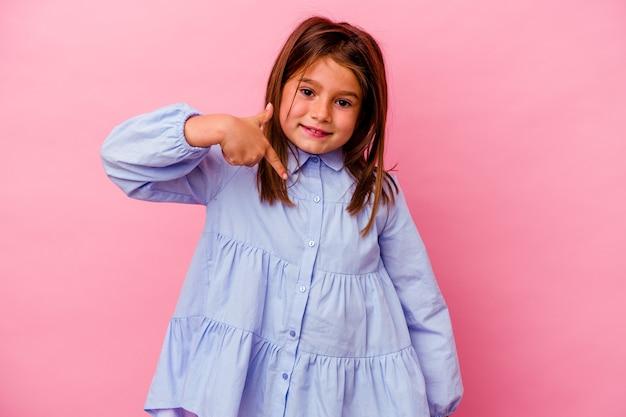 Menina caucasiana isolada na parede rosa pessoa apontando com a mão para um espaço de cópia de camisa, orgulhosa e confiante
