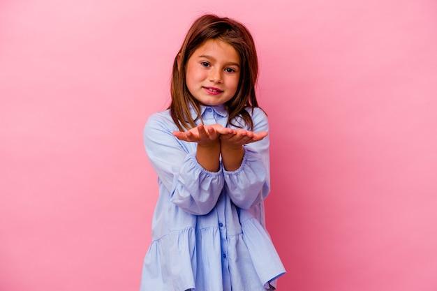 Menina caucasiana isolada na parede rosa segurando algo com as palmas das mãos, oferecendo-se para a câmera.