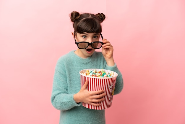Menina caucasiana isolada na parede rosa surpresa com óculos 3d e segurando um grande balde de pipocas