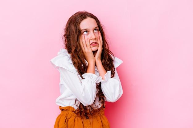 Menina caucasiana isolada na rosa choramingando e chorando desconsoladamente.