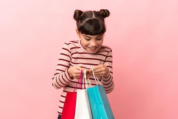 Menina caucasiana isolada na rosa segurando sacolas de compras e olhando dentro delas