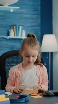 Menina caucasiana lendo livro na mesa para trabalhos da escola primária