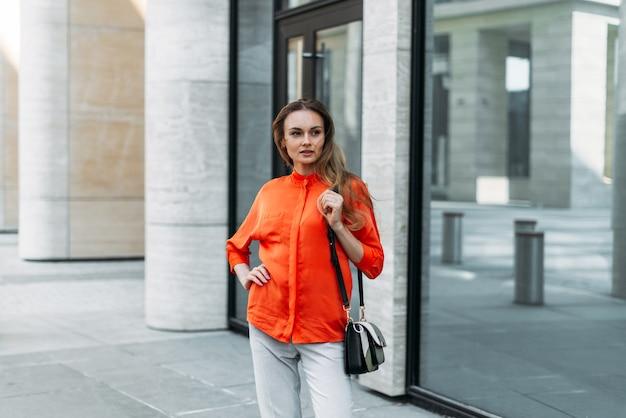 Menina caucasiana na cidade no verão está esperando por uma reunião