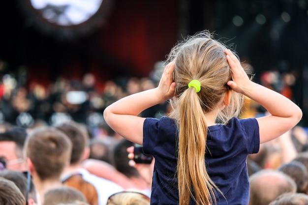 Menina caucasiana nos ombros do pai assistindo o concerto no meio da multidão.