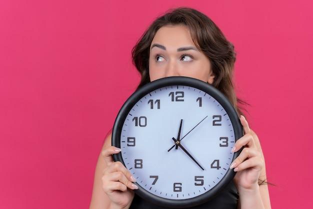 Menina caucasiana pensativa com camiseta preta segurando um relógio de parede no fundo rosa
