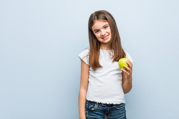 Menina caucasiana pequena segurando uma maçã verde feliz, sorridente e alegre.