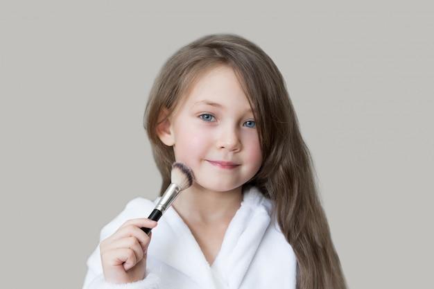 Menina caucasiana pinta o rosto com pó de maquiagem.