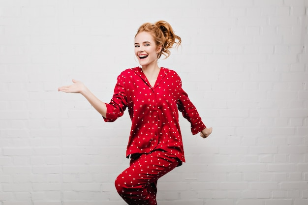 Menina caucasiana positiva magro em roupa de noite vermelha na moda dançando na parede de tijolos. foto interna da bela jovem branca de pijama se divertindo em casa.