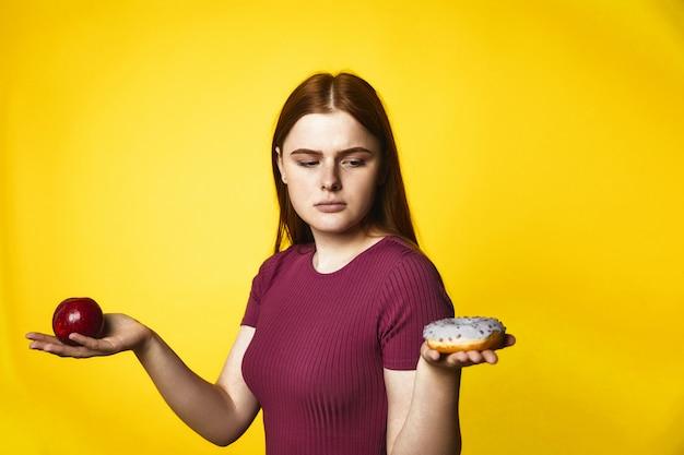 Menina caucasiana ruiva pensativa está segurando a maçã em uma mão e donut em outra