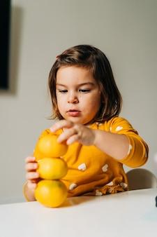Menina caucasiana se divertindo com tangerinas. dieta de criança saudável. reforço imunológico com vitamina c