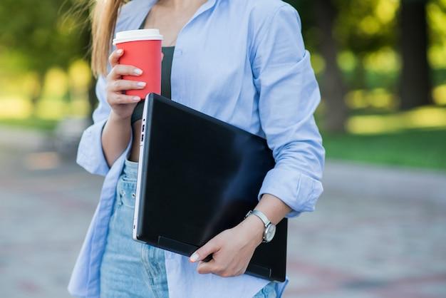 Menina caucasiana segurando laptop e uma xícara de café