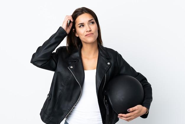 Menina caucasiana segurando um capacete de motocicleta no fundo branco, tendo dúvidas e confusa expressão facial