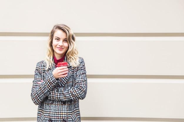 Menina caucasiana, segurando um copo vermelho com café para ir.